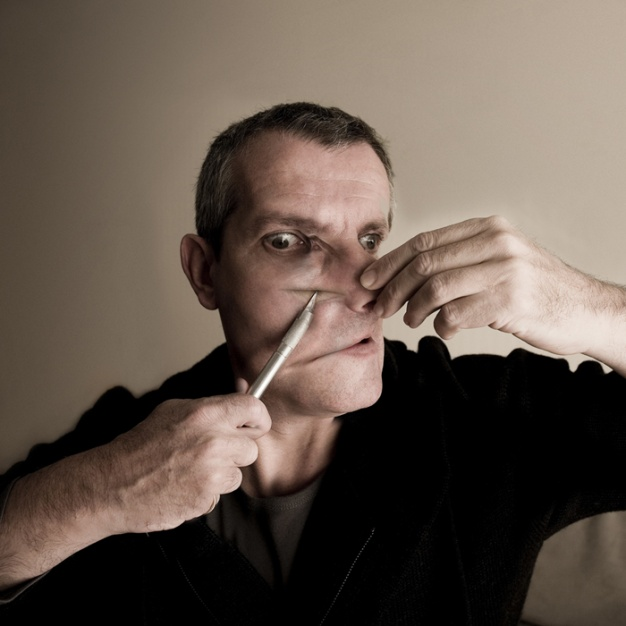 MAN ALTERING HIS FACE WITH A SCALPEL