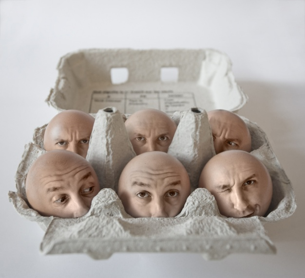MEN HEADS IN AN EGG BOX
